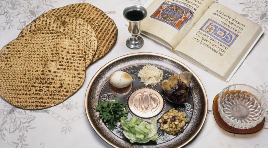 Een seder-schotel met symbolische gerechten, links drie ronde matses en een beker rode wijn, rechts een schoteltje en een boek